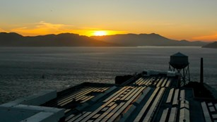 sun setting over a body of water and mountains, water tank and roof with solar panels in foreground