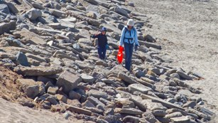 woman and child walking along rocks. woman is holding plastic bag