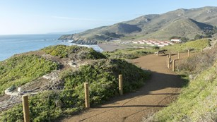 A trail runs across the hills overlooking a beach and red roofed buildings.