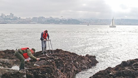 Researchers in life jackets conduct rocky intertidal monitoring.