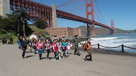 Group of youth walk away from Fort Point with two ranger