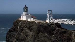 white lighthouse and suspension bridge atop cliff edge surrounded by ocean
