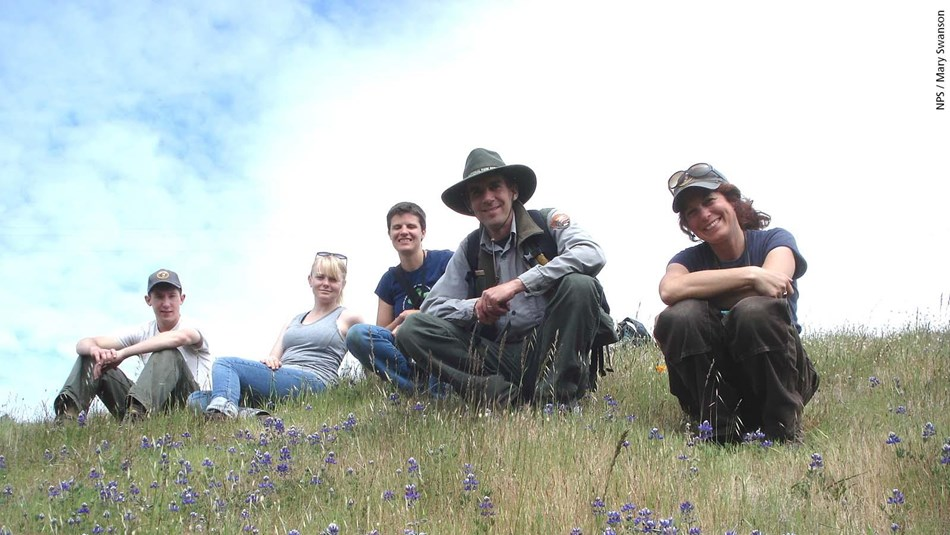 Natural resources staff and volunteers pause for a photo on a flower-filled hillside.