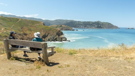 Two individuals sit on a wooden bench overlooking coastal bluffs and the Pacific ocean.