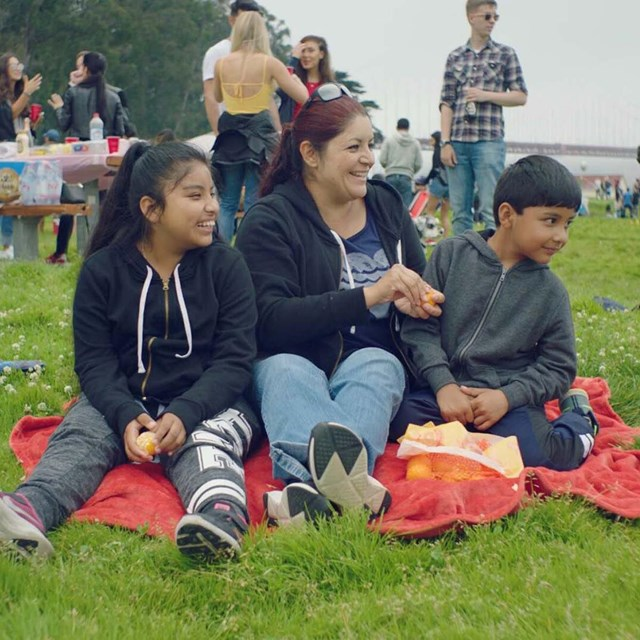family shares red picnic blanket on crissy field