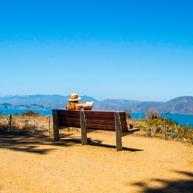 Visitor enjoying view from park bench on the Land's End trail