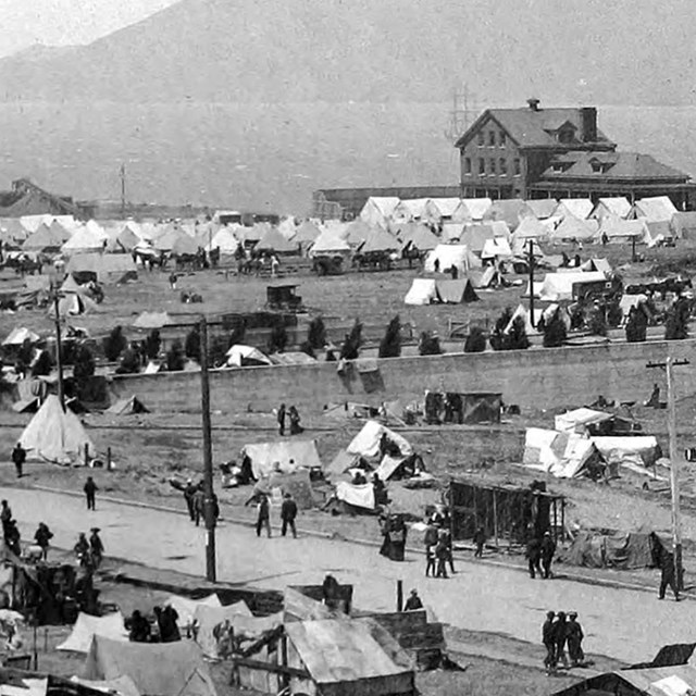 army tents and buildings along waterfront of old fort mason