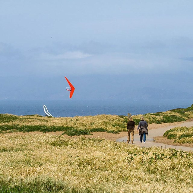 two people walk on trail with hang glider passing by