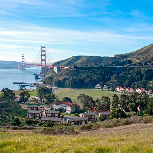Buildings of Fort Baker nestled in the hills of the foreground, Golden Gate bridge & SF Bay behind