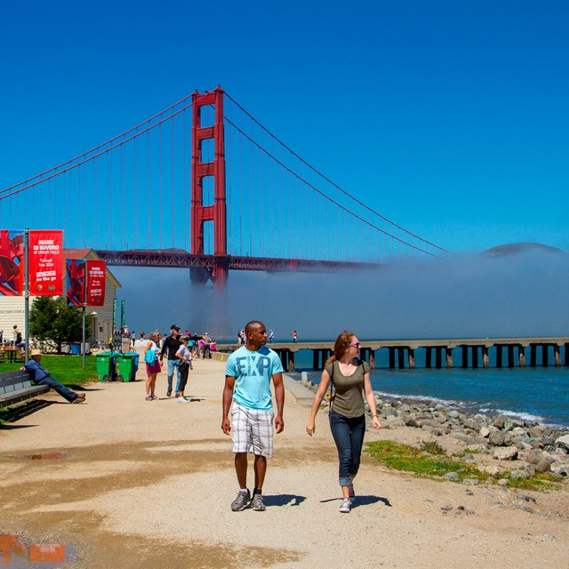 two people walk on Crissy Field with Golden Gate Bridge in the background