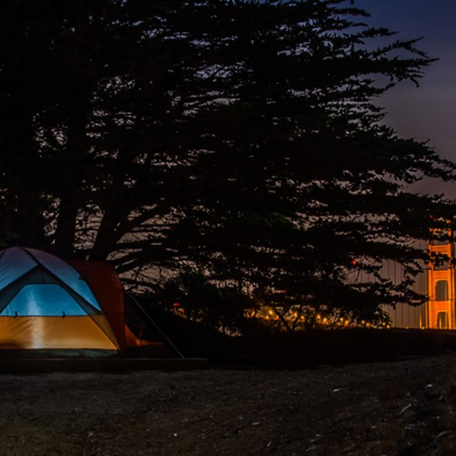 tent on ground with lit golden gate bridge in background