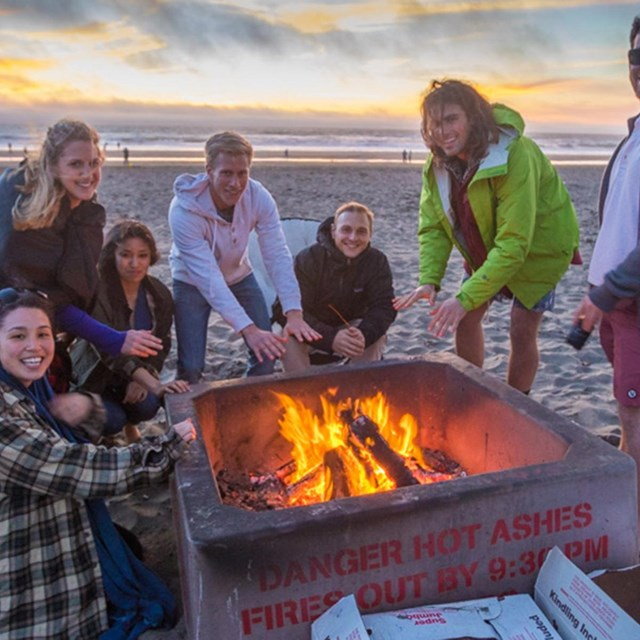 group of men and women gathered around fire on ocean beach
