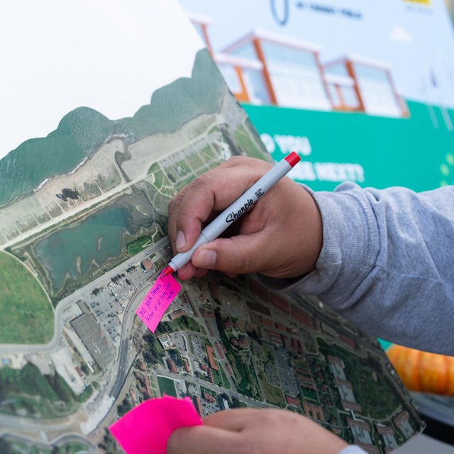 Hand writes on post-it notes over a map