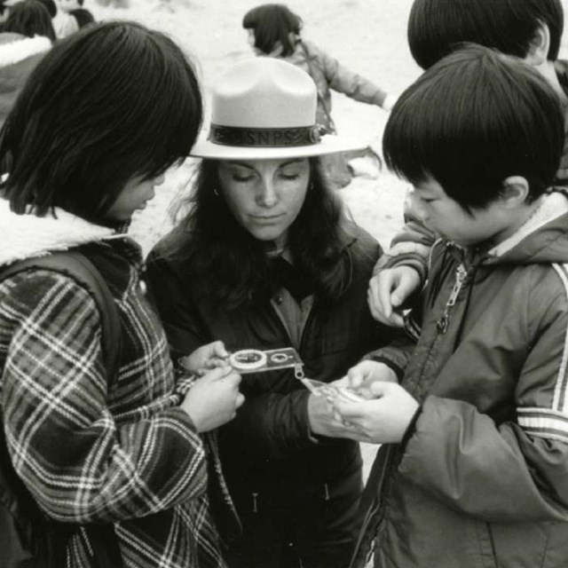 A black and white photo of a ranger looks at a hand lens with two youths.