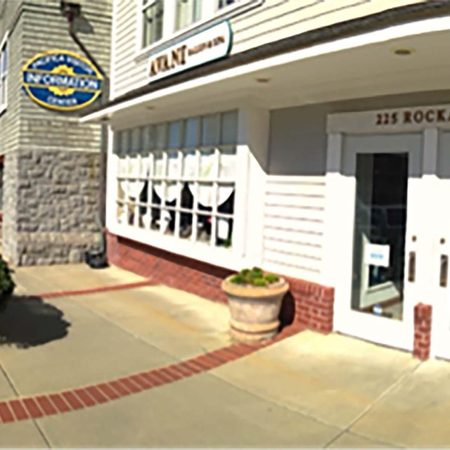 front of door of visitor center with 225 Rockaway on the frame