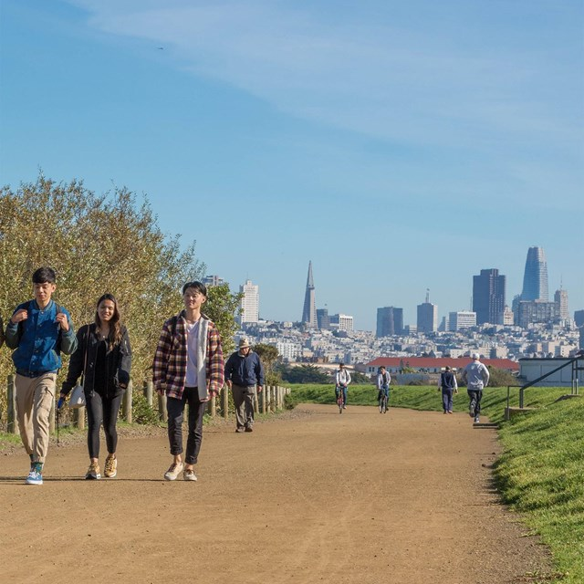 people walking along a wide gravel path at Crissy Field with San Francisco skyline behind