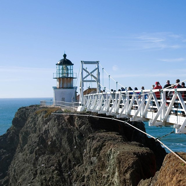 People walk on draw bridge leading out to Point Bonita