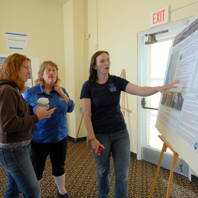 People discussing a park science poster
