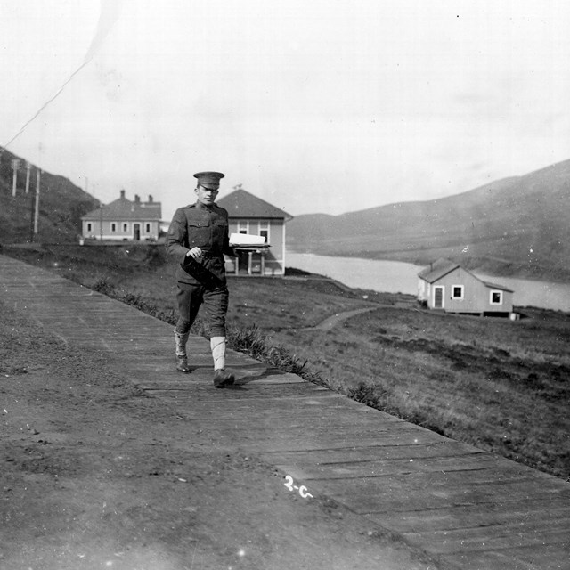 Historic photo of soldier on boardwalk with buildings of Fort Barry and Rodeo Lagoon behind