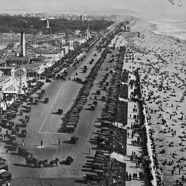 Historic photo of a crowded Ocean Beach and parking lots full of 1920s cars