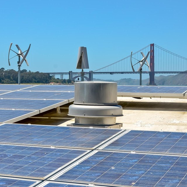 Solar panels on roof by Crissy Field with Golden Gate Bridge in background.
