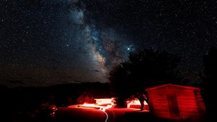 Milkyway over a red lit Lehman Caves Visitor Center, with a historic cabin in foreground.
