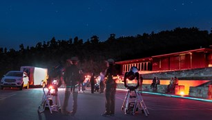 Telescopes set up in the parking lot with red lit visitor center in background