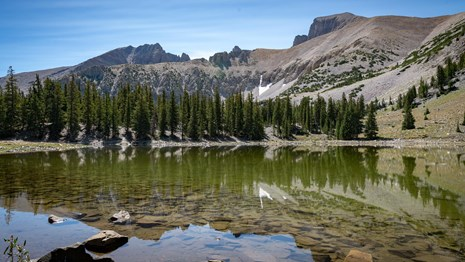 Reflection of Wheeler Peak in the still waters of Stella Lake under a clear blue sky.