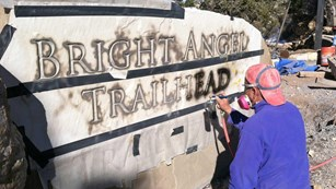A worker airbrushing on the letters of the Bright Angel Trailhead.