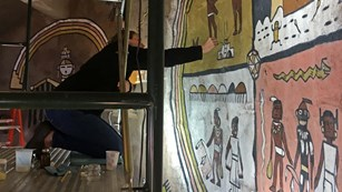 A conservator on a scaffolding renovating a mural in Desert View Watchtower.