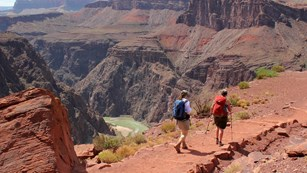 Two hikers walking on a dirt trail. Beyond them the river within a steep granite gorge.