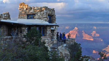 A stone building on the edge of the canyon at sunset.