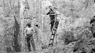 A black and white photo of two men installing a telephone pole.