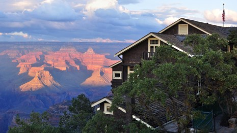 A building blocked by a tree with the Grand Canyon in the background