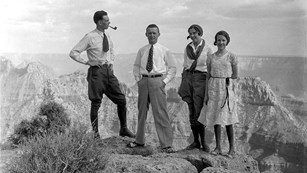 Historic photo of 2 men and 2 women standing on the edge above a large canyon.