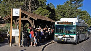 Visitors boarding a park shuttle bus from under a covered bus stop shelter