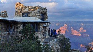 A stone building with the Grand Canyon in the background.
