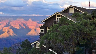 A brown building covered by trees with the Grand Canyon in the background.