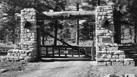 A black and white photo of the gate of the Pioneer Cemetery.