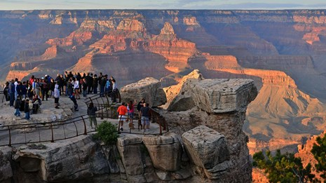 Crowd of visitors at a scenic overlook and watching orange light of sunset falling on Grand Canyon