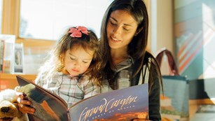 A woman is reading from a large picture book to her young daughter