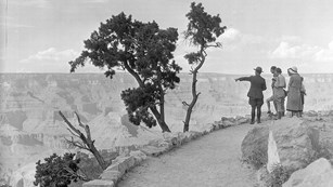 black and white photo from 1930's of park ranger escorting well dressed visitors on rim trail.