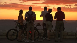 Five people in silhouette are watching a colorful sunset. Two have bicycles.