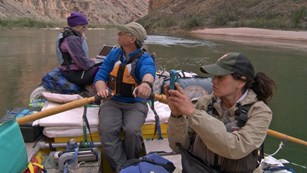 Three scientists in a raft on a green river. One is photographing, one is rowing, one with a laptop.