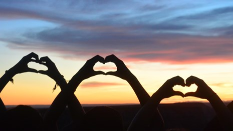 three youth make heart shapes with their hands in front of a sunset