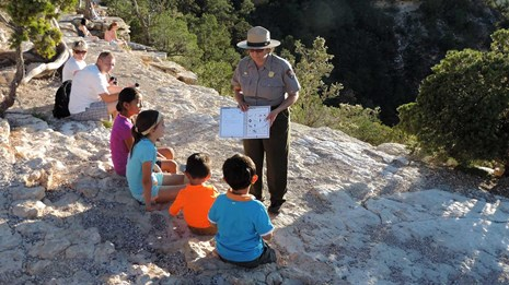 A ranger helps a group of four kids with there Junior Ranger book.