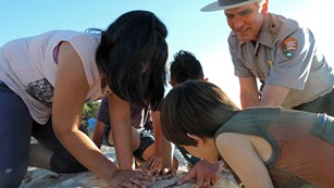 A park ranger points out fossils for a few kids.