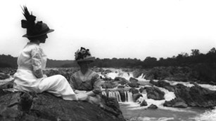 Two women sit on a cliff and enjoy viewing the Great Falls of VA
