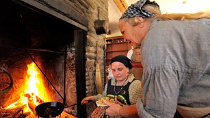 Two women cooking in the kitchen fireplace.