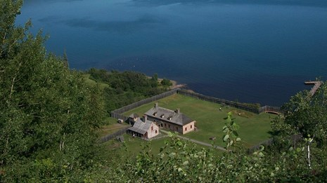 Overview looking down at Historic palisade, Great Hall and other buildings with Lake Superior